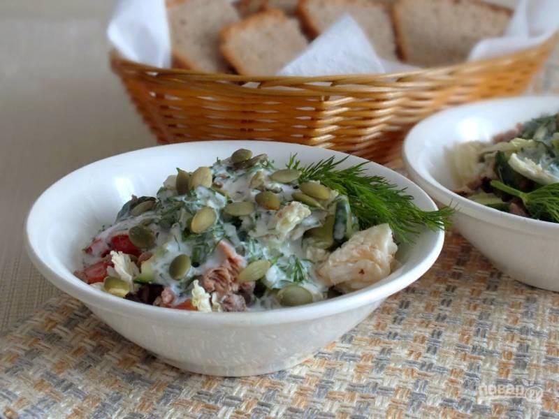 Салат перемешайте. Полейте заправкой и посыпьте тыквенными семечками.
