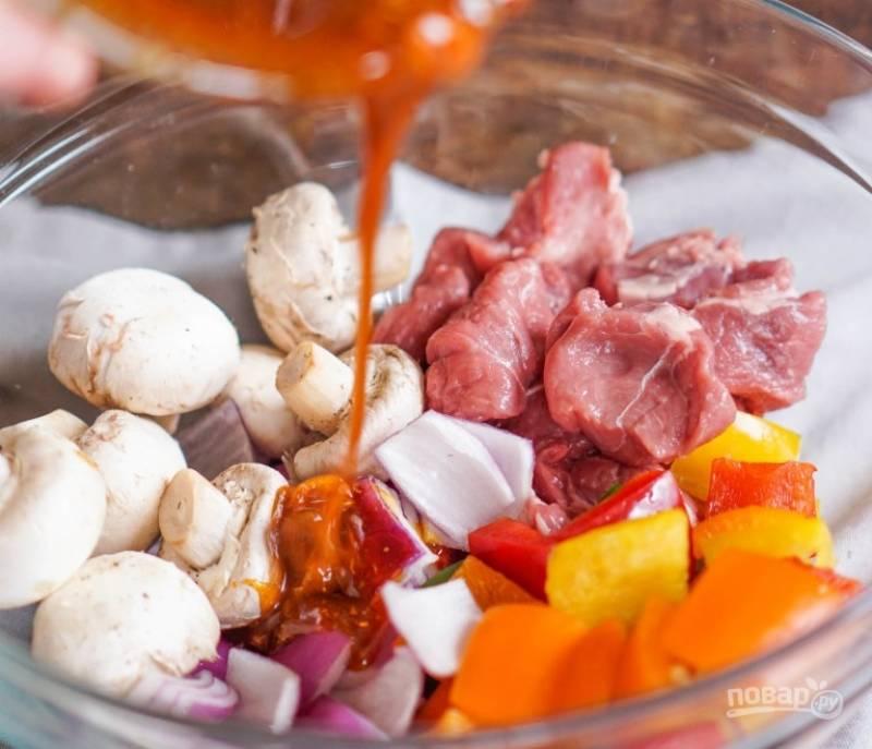 1.Нарежьте мясо кусочками, очистите перец от семян и лук от шелухи, нарежьте все крупно. Вымойте грибы, сложите все ингредиенты в миску. Смешайте оставшиеся ингредиенты для маринада и залейте содержимое миски с овощами.