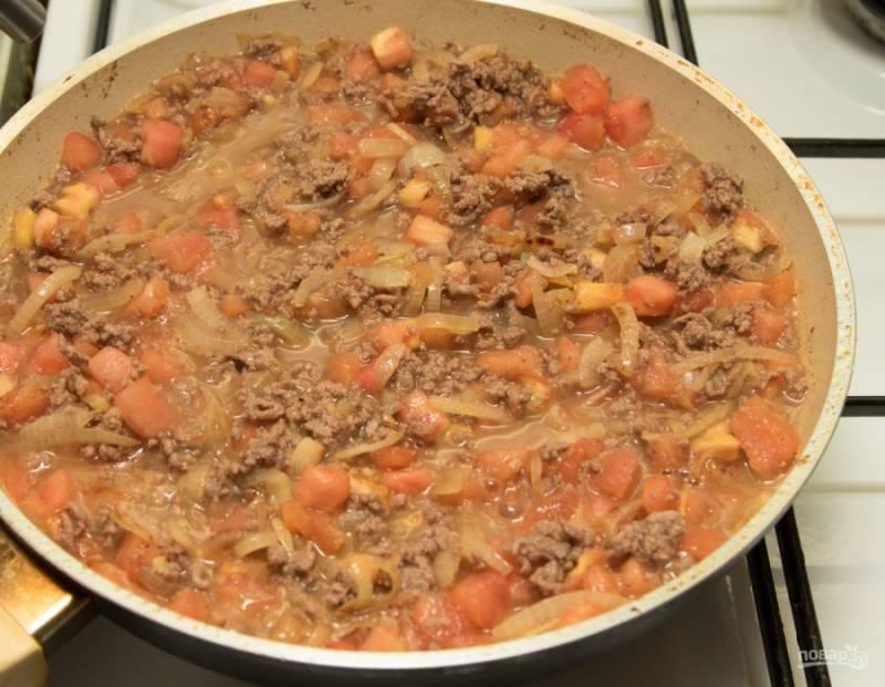 Добавьте к фаршу лук, помидоры, вино, соль, перец, корицу и тушите до полного выпаривания жидкости.
