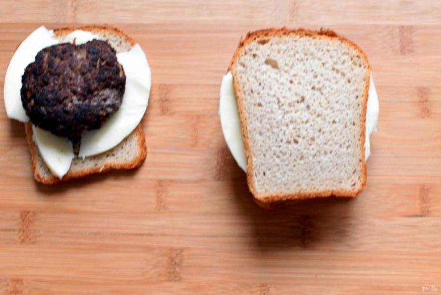 На ломтик тостового хлеба выложите ломтик сыра. Хорошо взять чеддер или моцареллу. Любители блюд попикантнее могут смазать накройте ее ломтиком сыра и хлебом. Слегка придавите бутерброд, делая его более плоским. Повторите процесс с оставшимися котлетами.