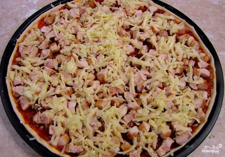 8. Вот и все, 15 минут — и начинка для пиццы готова! Поливаем соусом основу теста, а затем выкладываем наверх курицу с сыром и отправляем заготовку в разогретую до 180 градусов духовку на 15 минут.