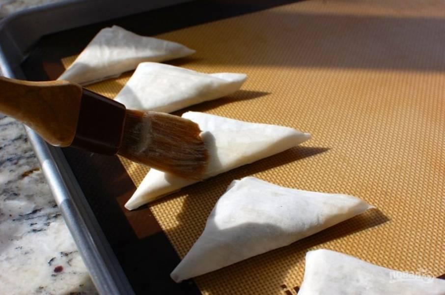 6.Выложите все пирожки на противень, смажьте каждый растопленным маслом.