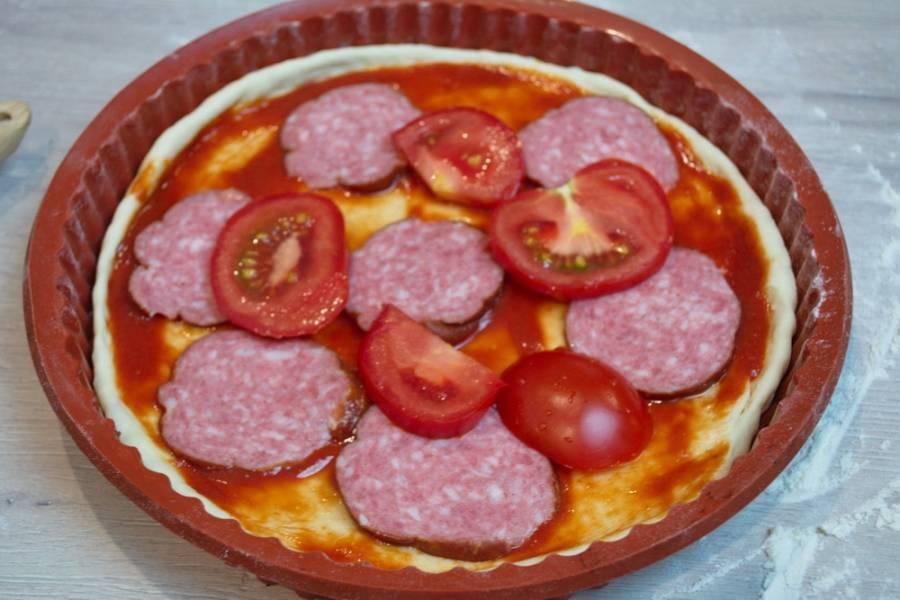 Распределите соус по всему тесту. Сверху выложите колбасу и нарезанные томаты.