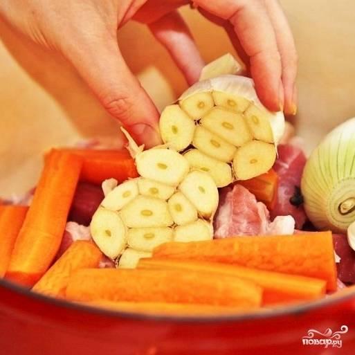 Морковь разрезаем на несколько частей, головку чеснока разрезаем пополам. Добавляем в кастрюлю.