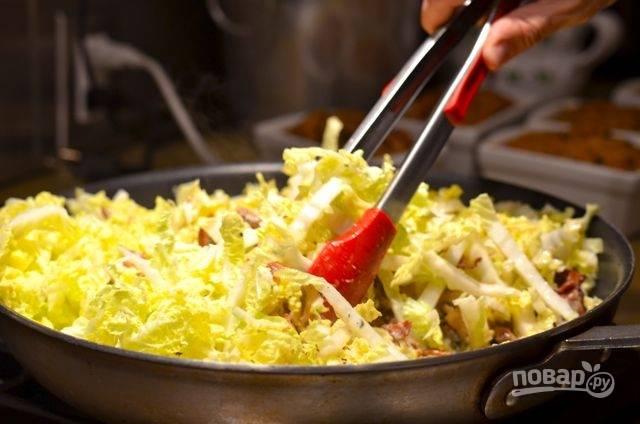 7.Вымойте и нашинкуйте китайскую капусту, добавьте ее в сковороду и перемешайте щипцами, влейте заправку и прогрейте содержимое несколько минут.