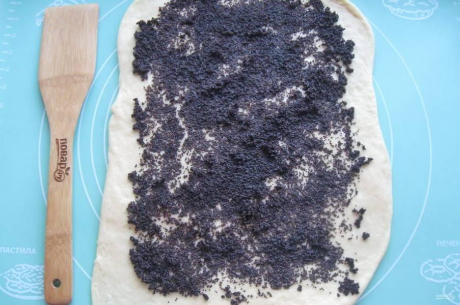 После тесто достаньте из миски, обомните. Разделите на две неравные части. Большую часть раскатайте в пласт и выложите начинку из мака. Такая начинка продается уже готовая с сахаром, но её можно приготовить самим. Мак залейте небольшим количеством воды и проварите 7-10 минут. После воду слейте, добавьте сахар по вкусу и разотрите ступкой или измельчите в кофемолке.