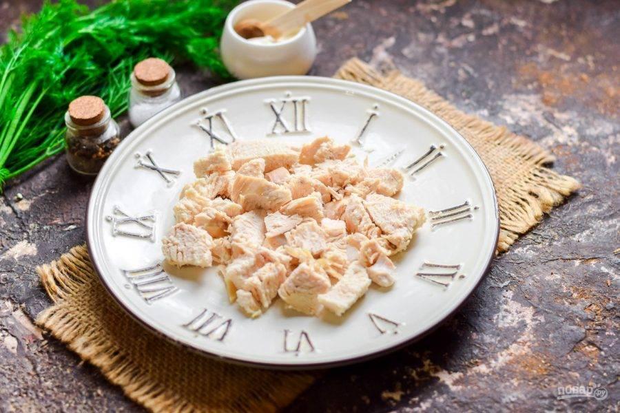 Возьмите тарелку для салата. Вареное куриное филе нарежьте небольшими кусочками и переложите в салат - это будет первый слой.
