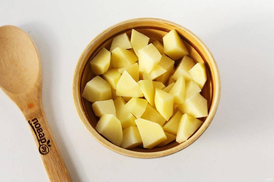 Картофель нарежьте кубиками и тоже отправьте в кастрюлю.