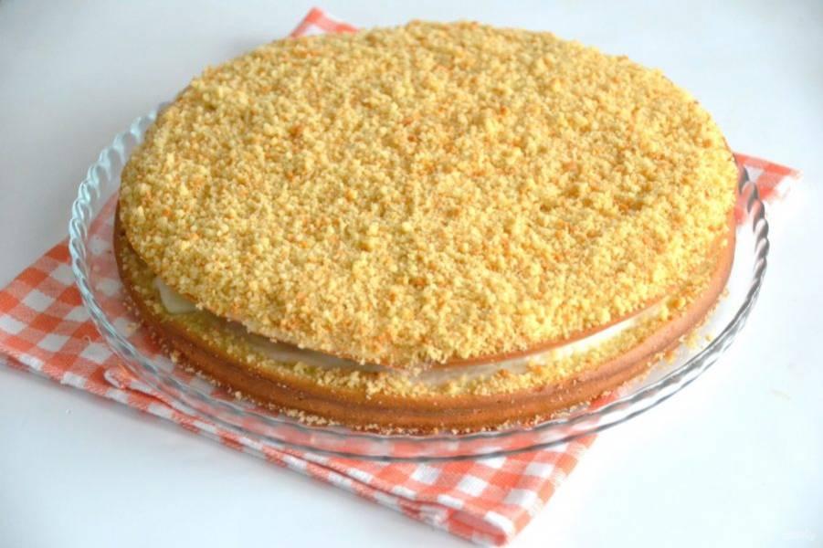 Обсыпьте верх сметанника бисквитной крошкой. Дайте пирогу настояться в холодильнике примерно 2 часа, чтобы сметанный крем хорошо пропитал коржи.