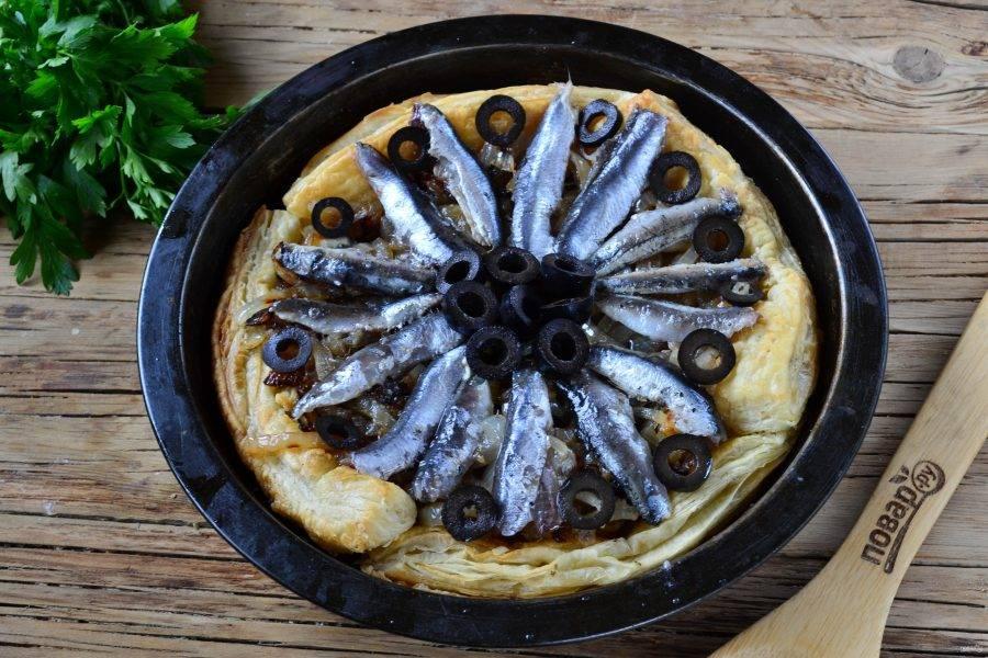 Кильку очистите от головы, хребта и хвостика, выложите сверху на луковую начинку. В середину положите маслины.