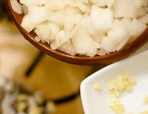 Лук и чеснок почистите и порежьте мелким кубиком. Сложите в кастрюлю и обжарьте на растительном масле до золотистого цвета.