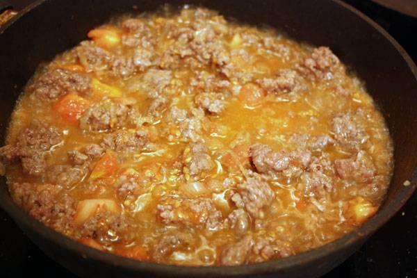 На сковороде разогреваем растительное масло и обжариваем на нем нарезанный лук до прозрачности. Добавляем фарш, жарим все вместе до полной готовности фарша, а затем добавляем мякоть помидор.