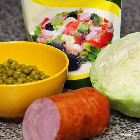 Подготовим все ингредиенты: с горошка сольем воду, капусту помоем, колбасу очистим от кожуры.