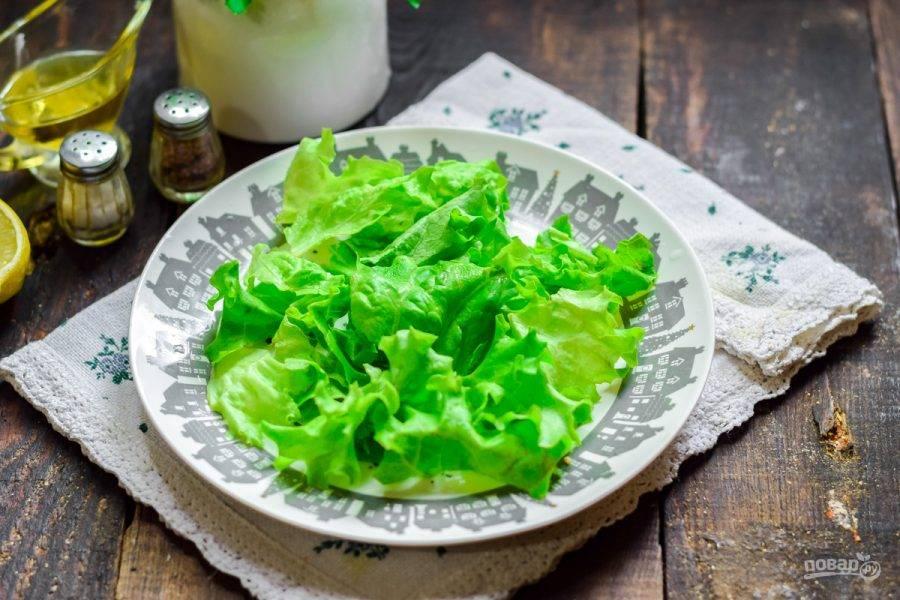 На тарелку выложите чистые салатные листья.