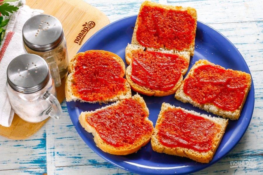 Ломтики хлеба любого сорта разрежьте пополам или же приобретите уже нарезанный хлеб. Обмажьте каждый ломтик кетчупом. Лучше всего использовать кетчуп без добавок, не горький и не пряный.