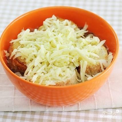 7. Включите духовку нагреваться на 200 градусов. Суп разлейте по тарелкам. В каждую выложите по пару кусочков французского батона. Каждый кусочек батона присыпьте тертым сыром.