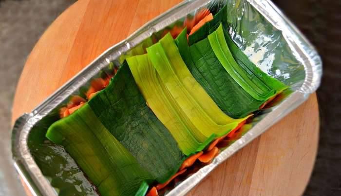 5. Тем временем из сырой моркови нарезаем длинные полосы при помощи специального ножа (подойдет нож и для чистки картофеля). Лук-порей и морковь заливаем кипятком и оставляем на 10 минут. После этого выкладываем их в форму, в которой будем готовить суфле.