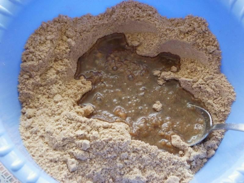 Сахар растворите в половине стакана кипятка. Полученный сироп остудите. Добавьте его к измельченному печенью.
