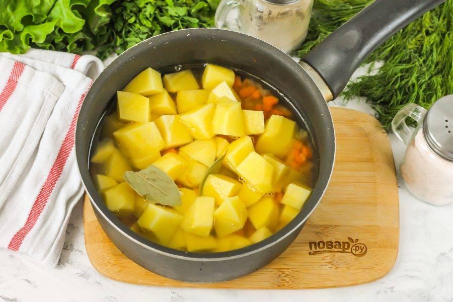 Картофель нарежьте средними кубиками и высыпьте в емкость. Влейте горячую воду и посолите, добавьте лавровые листья и отварите картофель примерно 15 минут.