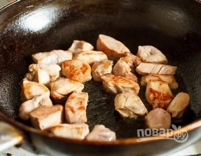 4. На сковороду тем временем добавьте еще немного масла и выложите нарезанную небольшими кусочками свинину. Обжарьте на сильном огне до румяности.