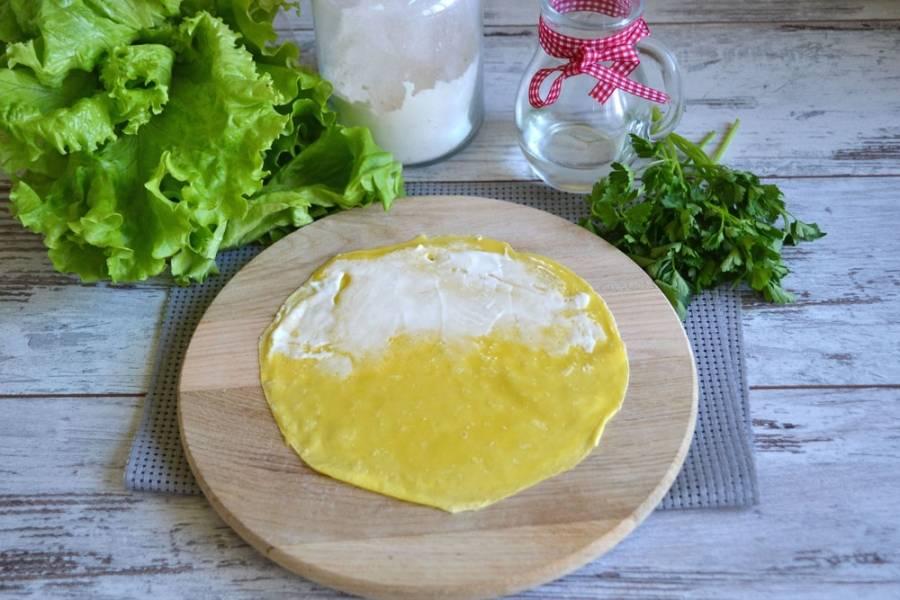 Сформируйте роллы: половину блинчика смажьте тонким слоем сыра.