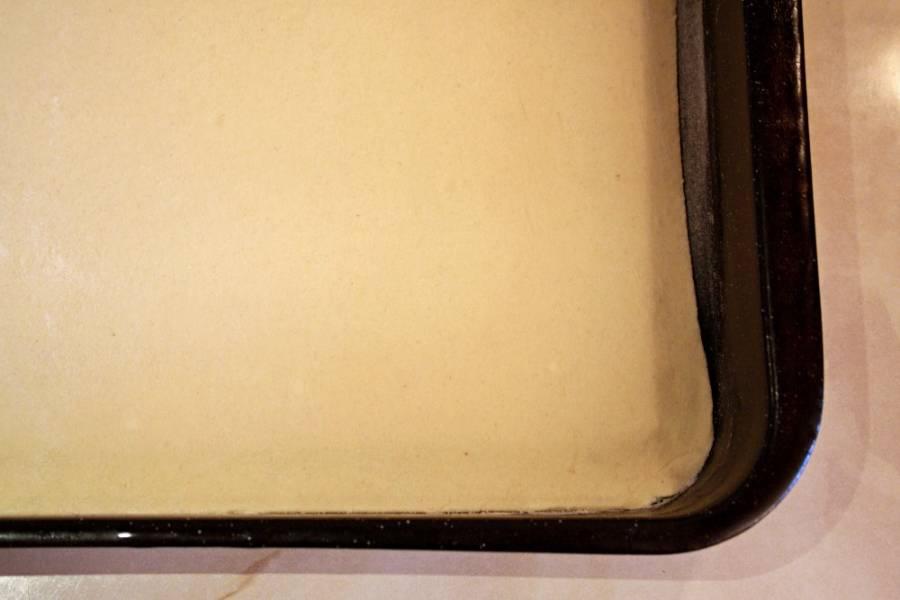 Тесто раскатайте в пласт и разрежьте пополам. Одну половину выкладываем на смазанный маслом противень.