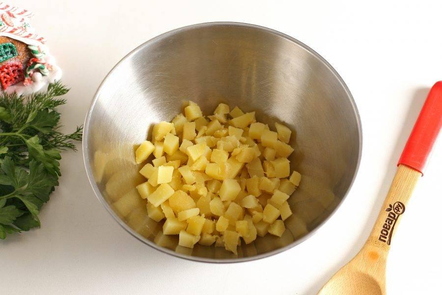Картофель очистите, нарежьте мелкими кубиками и сложите в глубокую миску.