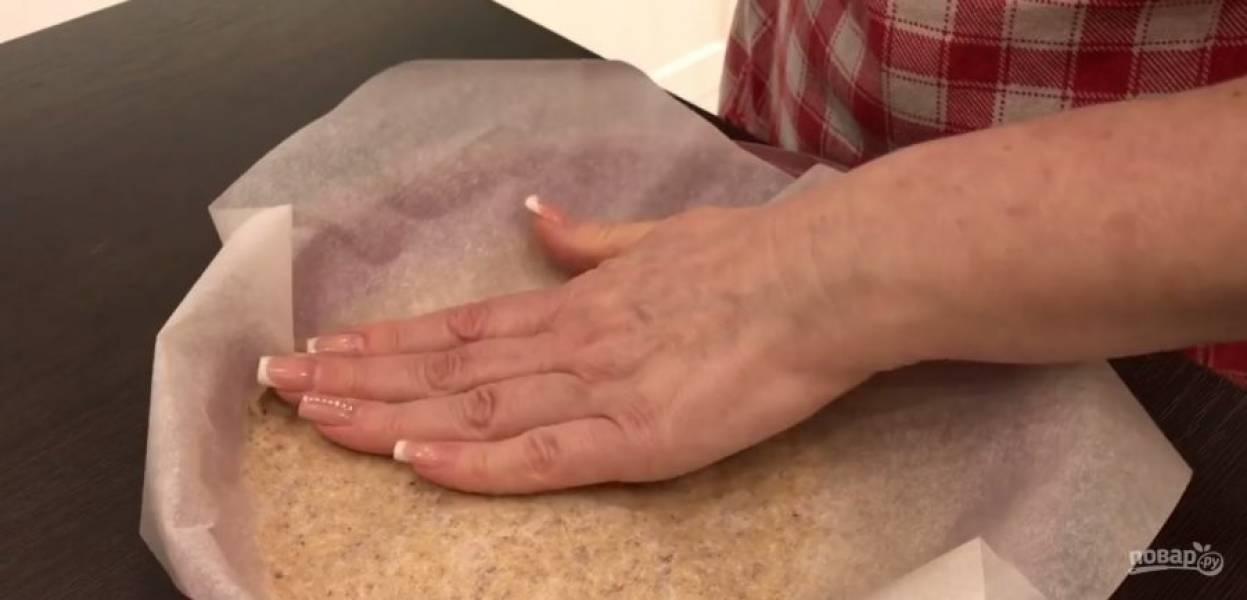 3.  Оставьте тесто на 15-20 минут. Равномерно распределите тесто в покрытой пергаментом форме так, чтобы его толщина не превышала 1 см. Накройте тесто пергаментом и расправьте тесто руками.