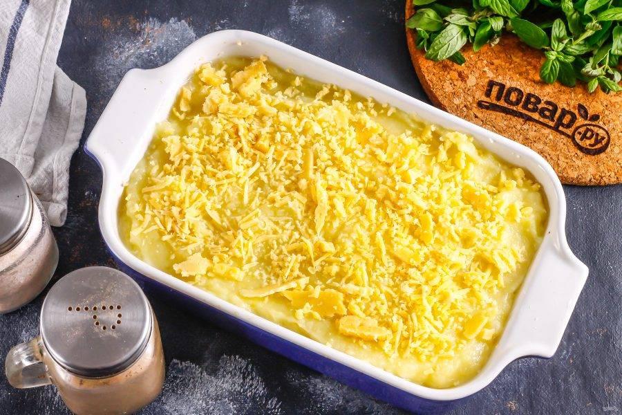 Выложите сверху оставшееся пюре из картофеля, натрите поверх него твердый сыр. Поместите форму в разогретую до 180 градусов духовку.