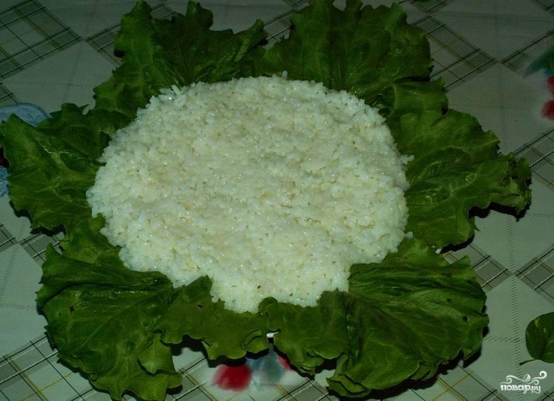 На дно салатницы укладываем листья салата. Сверху кладем слой риса.