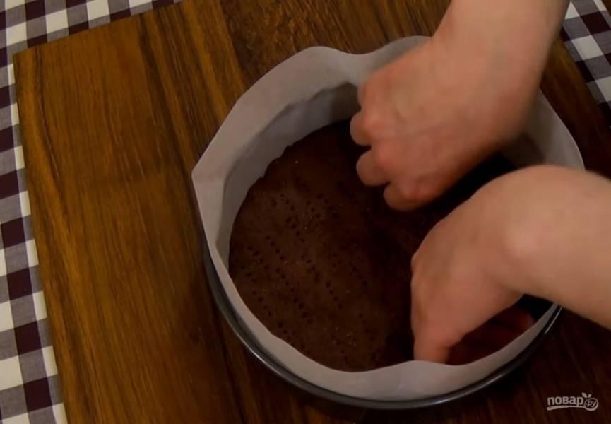 3. Выпекайте в разогретой до 200 градусов духовке 10 минут. Дайте коржу остыть, выньте его из формы. Застелите бортики формы пергаментной бумагой и снова положите в нее корж.