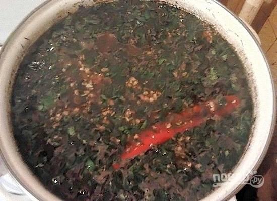 Очистим чеснок, измельчим зелень и перетрем все вместе с солью. Добавляем в суп, когда рис будет готов.