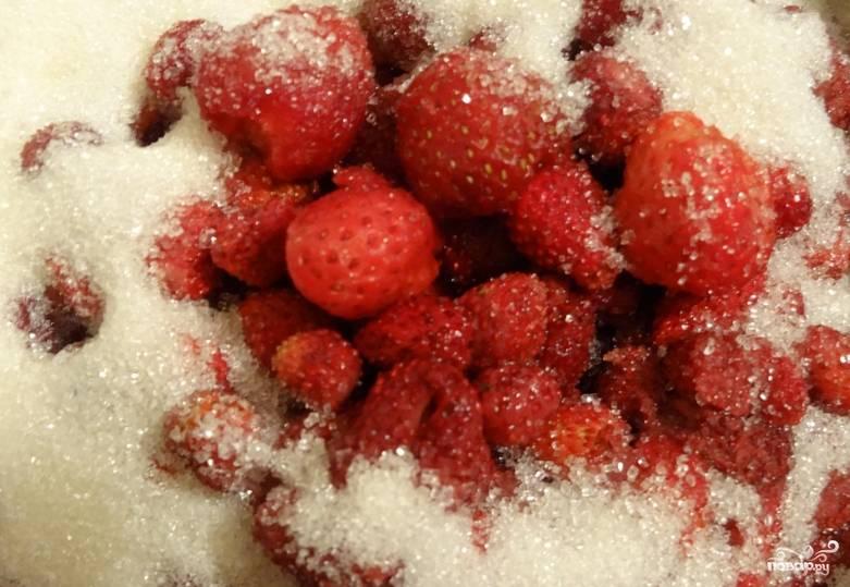Засыпьте ягоды половиной сахара. Поставьте в прохладное место на 1 час, чтобы земляника пустила сок.