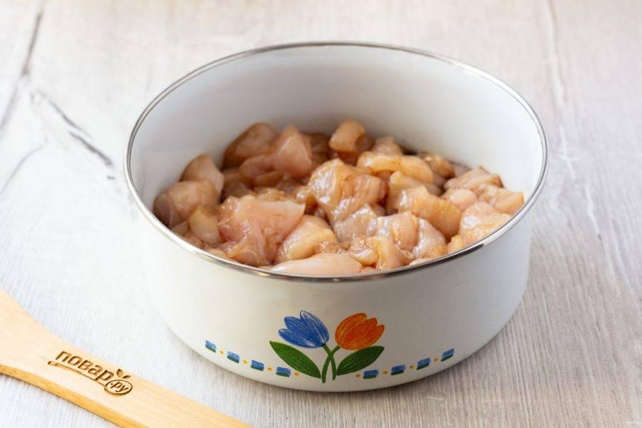 Филе грудки помойте и нарежьте на кусочки. Залейте соевым соусом и уберите в сторону. Пока будем заниматься подготовкой и обжаркой овощей, курица немного замаринуется.