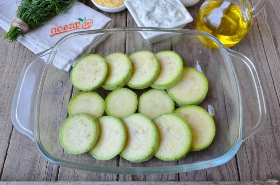 Кабачки порежьте кружочками, посолите и поперчите. Противень смажьте растительным маслом. Выложите кабачки в один ряд или внахлест.