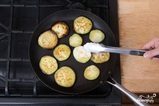 2. На сковороду налейте немного масла. Баклажаны подсолите немного и выложите на сковороду. Обжарьте на среднем огне с двух сторон до румяности. Снимите и отложите пока в сторону.
