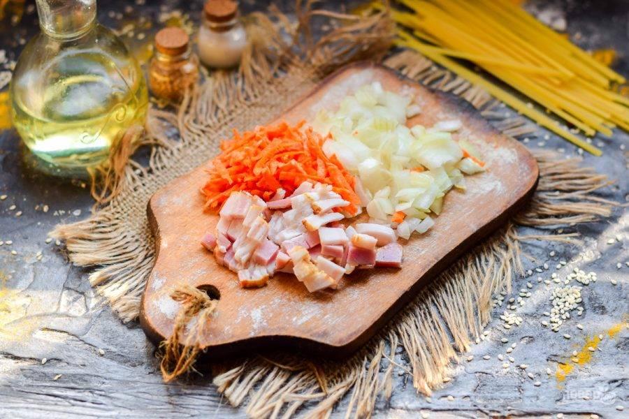 Нарежьте мелко бекон, очистите овощи. Морковь натрите стружкой, лук нарежьте небольшими кубиками.