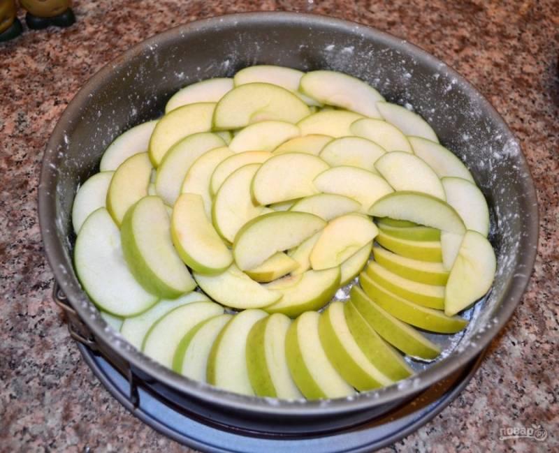 2. Нарежьте яблоки полукольцами. Форму для выпекания смажьте маслом и присыпьте немного мукой. Теперь нужно выложить яблоки так, чтобы не оставалось промежутков.