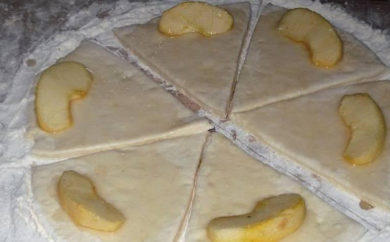 Разрезаем пласт на 6-7 треугольников. На широкий край каждого треугольника выкладываем яблоки.