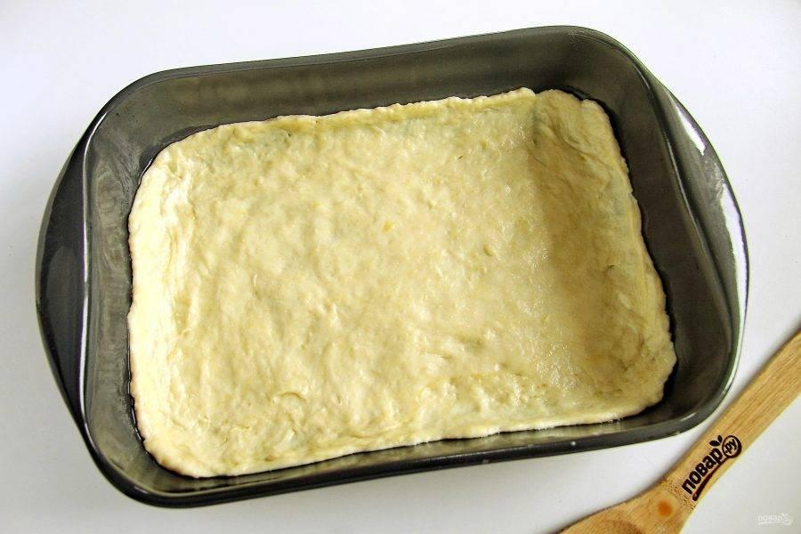 Смажьте форму для выпечки и руки растительным маслом. Тесто разделите на две неравные части. Ту часть, что побольше, распределите руками по дну формы, не забывая сделать высокие бортики. Сладкая начинка обязательно даст сок, который может без бортиков вытечь из пирога.