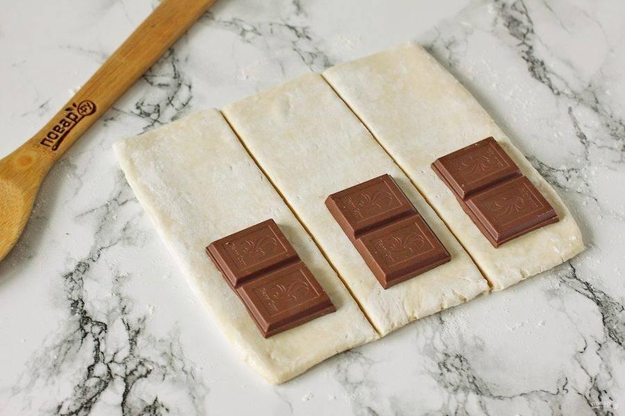 На каждую полоску теста, ближе к одному краю, положите немного шоколада. Шоколад можно как поломать руками, так и измельчить ножом.