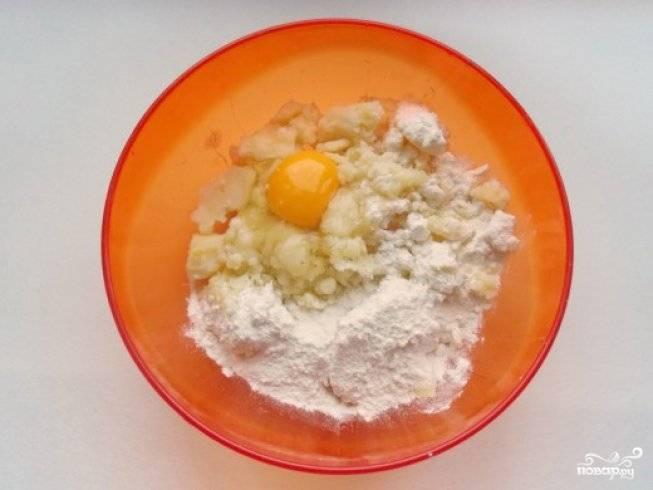 Чтобы приготовить картофельное тесто, сварите очищенный картофель до готовности. Затем, пока он ещё тёплый, разомните его толкушкой в пюре. Сюда же добавьте яйцо, пшеничную муку и щепотку соли. Всё хорошо перемешайте.