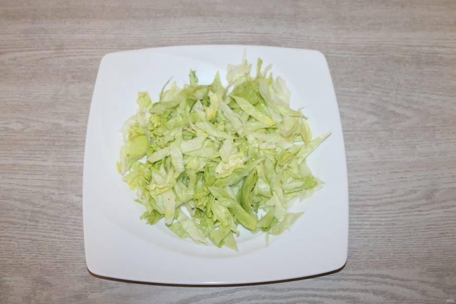 Салат айсберг нарежьте произвольно. На большое блюдо выложите салат айсберг.