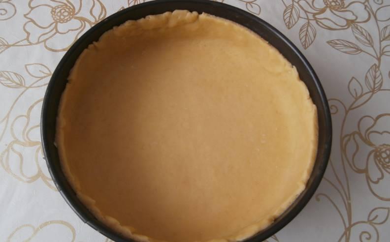 Просеиваем муку с разрыхлителем, затем растираем с размягченным сливочным маслом. Яйцо взбиваем с сахаром. Соединяем ингредиенты и замешиваем тесто, затем заворачиваем его в пищевую пленку и помещаем в холодильник на 25 минут. После чего раскатываем тесто и укладываем его в форму (25 см.), формируем бортики.