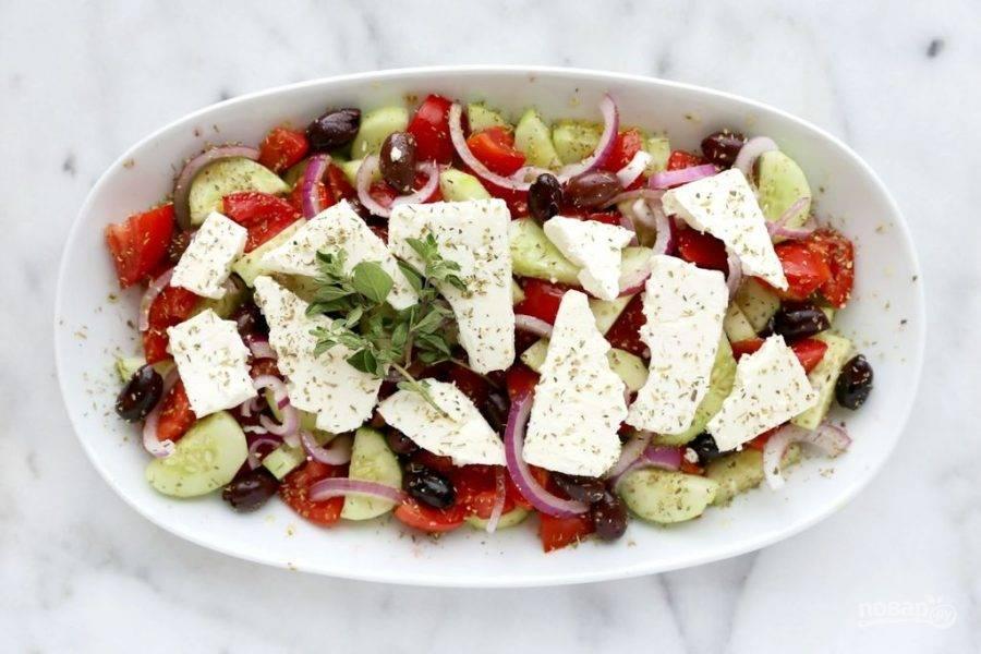 5.В миску выкладываю огурцы и томаты, перемешиваю. Затем добавляю лук и поливаю оливковым маслом, винным уксусом, выкладываю маслины и виноград, сверху выкладываю сыр. По вкусу кладу соль, орегано (сушеный), поливаю еще раз оливковым маслом и винным уксусом, украшаю веточками орегано.