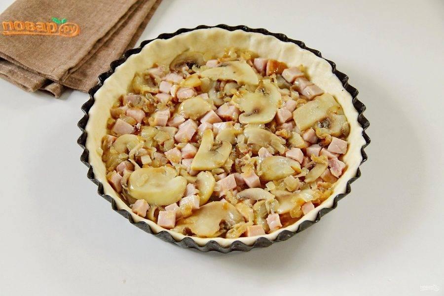 Обжарьте на сковороде нарезанный кубиками лук до мягкости, добавьте грибы и готовьте до испарения жидкости. В конце добавьте нарезанный кубиками карбонад, соль по вкусу и обжарьте все вместе около 1-2 минут. Выложите начинку на тесто и разровняйте.