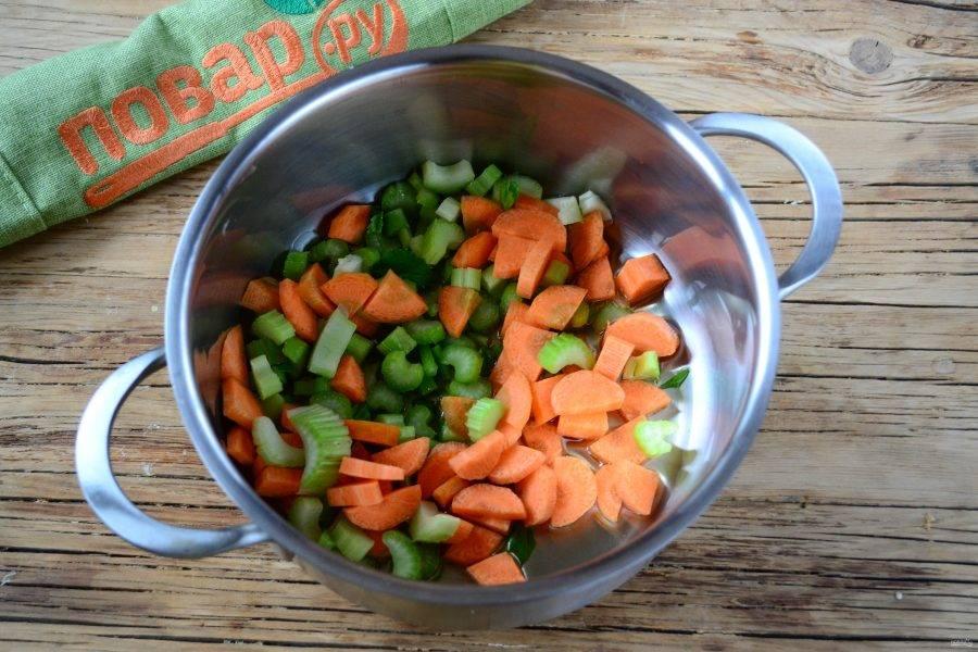 В толстодонной кастрюльке разогрейте растительное масло, добавьте морковь и сельдерей, пару минут прогрейте на среднем огне.