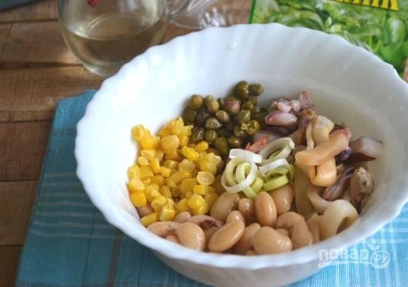5. Консервированную фасоль, кукурузу, каперсы соедините в глубокой мисочке. Туда же добавьте морепродукты и лук-порей.