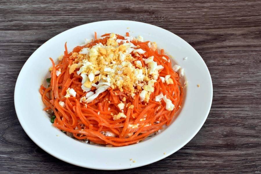 Выложите слой моркови по-корейски. Сверху уложите нарезанные кубиками яйца.