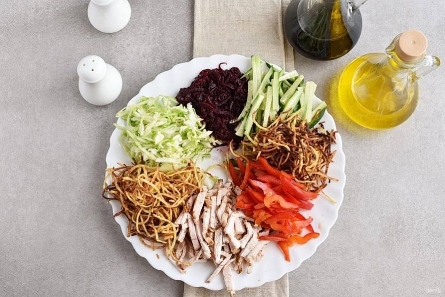 Свеклу натрите на корейской терке. Перец, огурец и буженину нашинкуйте соломкой вручную. Выложите ингредиенты на блюдо секторами по кругу. Картошку фри выложите двумя секторами.